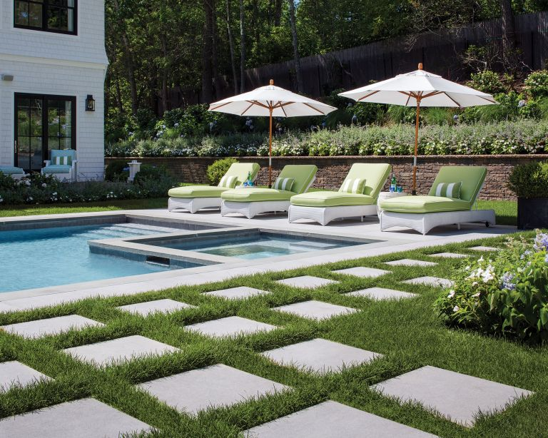 An example of pool patio ideas showing a swimming pool with pavers sunken into the lawn and a lounge area
