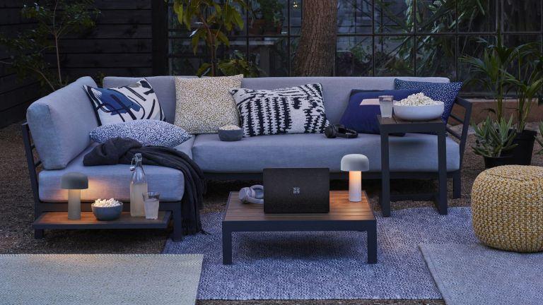 Courtyard garden ideas showing a corner sofa with outdoor rugs and garden lighting