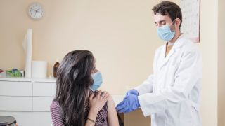 Woman with surgical mask receiving vaccine from doctor