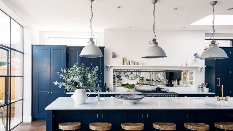 How to paint kitchen cabinets, illustrated in a white kitchen scheme with dark blue cabinetry and pendant lights over a marble breakfast island.
