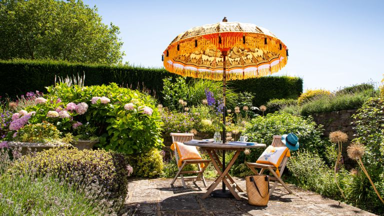 Roost episode 2 - patio with fringe parasol and outdoor furniture in large garden - Pic-credit-East-London-Parasol-Company