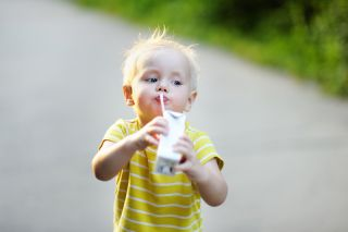 A toddler drinks juice from a juice box