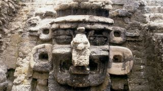 A mask of the rain god Chac decorates the facade of a pyramid at North Acropolis, in Mayan ruins, located in Tikal, Guatemala.