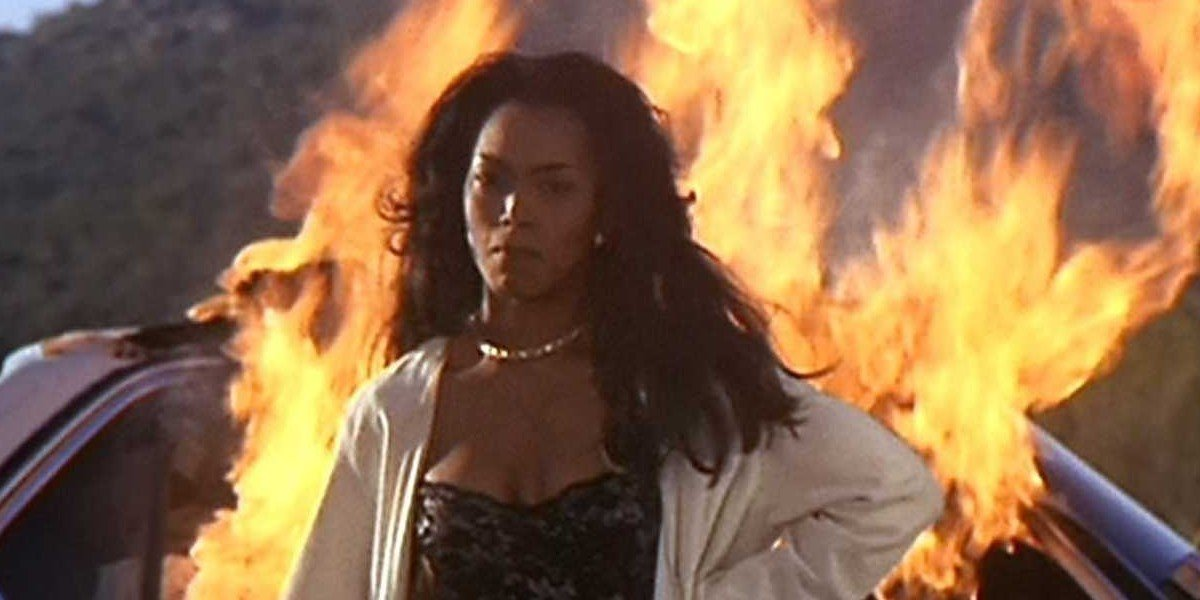 Angela Bassett in front of a burning car