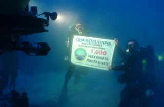 Divers Dave Pence (left) and Ken Longenecker (right) hold up a banner commemorating the Hawaii Undersea Research Laboratory's 1,000th dive with the Pisces submersibles.