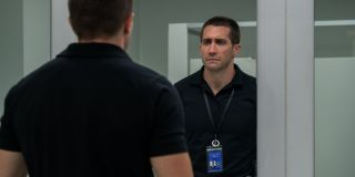 Jake Gyllenhaal looks at himself in the mirror sadly in The Guilty.