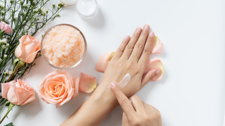 close up of swatch of moisturizer on hands surrounded by flowers