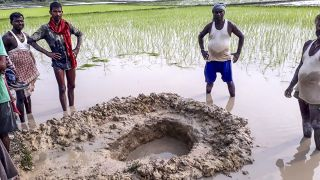 Locals crows around a crater created by the possible football-sized meteorite that fell in a rice field in the Mahadeva Village of the eastern state of Bihar in India.