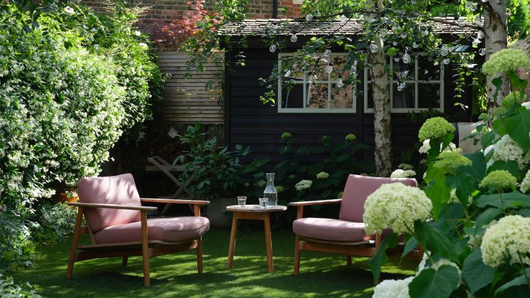 How to make a small garden look bigger: small garden with pink sitting and black shed