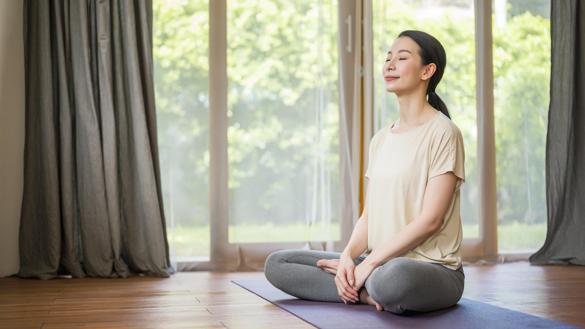 7 types of yoga: image shows woman doing yoga breathing exercises