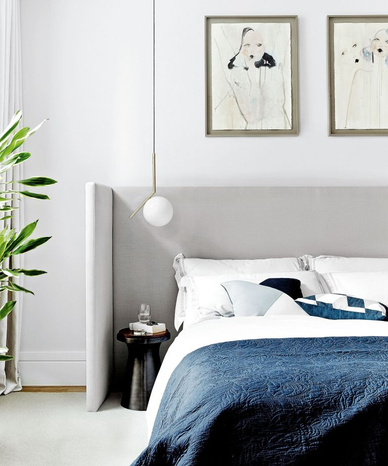 Modern bedroom lighting tips with a gray statement headboard and artwork on white walls.
