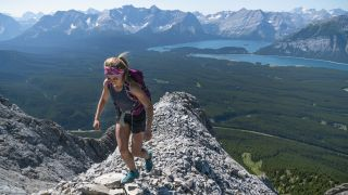 approach shoes vs hiking shoes: hiker on a narrow rocky ridge