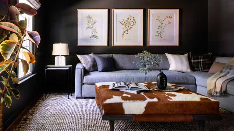 A living room with black painted walls, grey sectional sofa, brown cow hide footstool and artwork on the wall