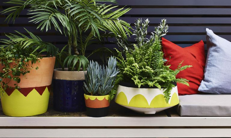terracotta pots painted in colourful patterns in a modern garden