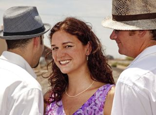 A woman with two men smiles.