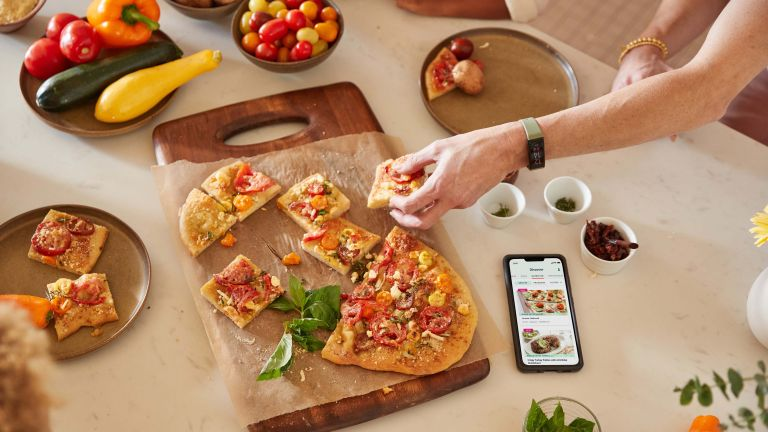 person reaching for a slice of pizza wearing the Amazon Halo View fitness tracker