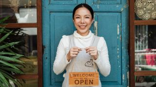 Website builder for small business: Woman holding up sign reading 'Open'