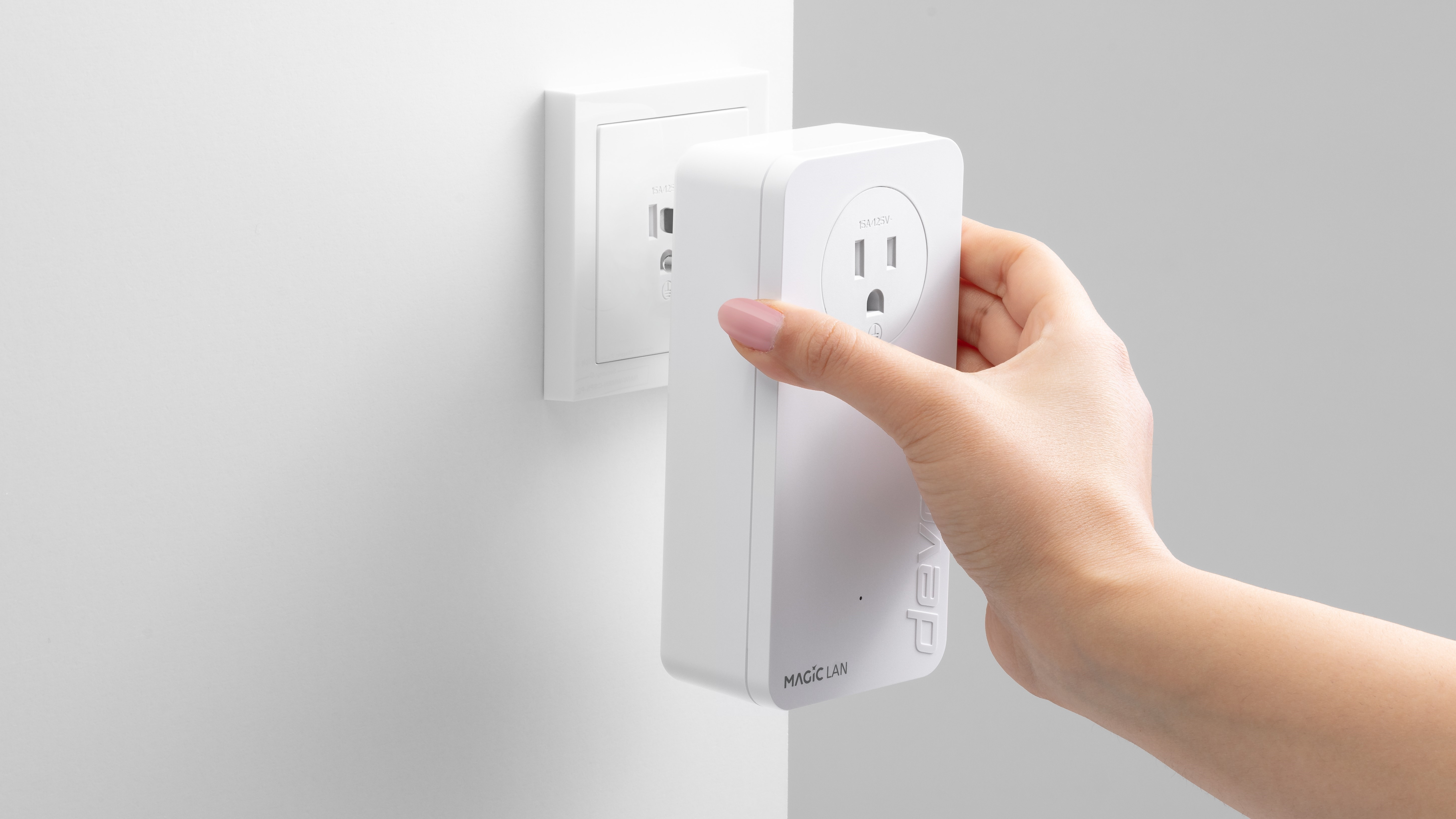 A hand plugging a devolo Magic 2 LAN triple powerline adapter into an electrical outlet.