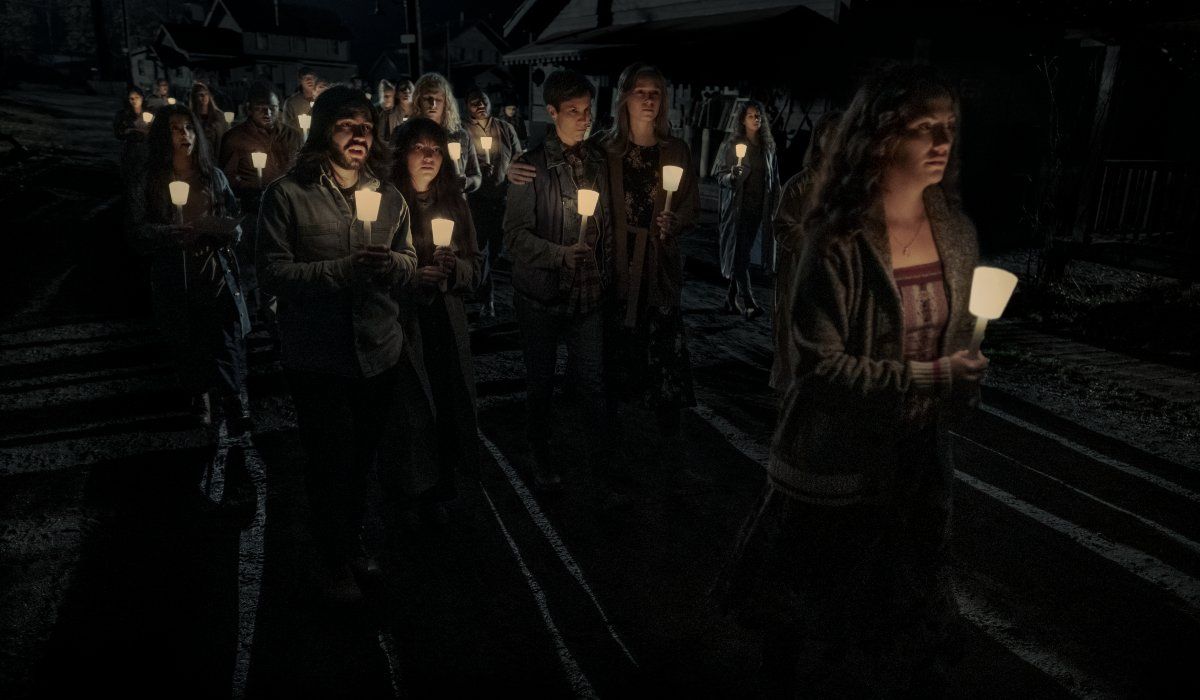 Townspeople walking in a candlelight vigil in Midnight Mass.