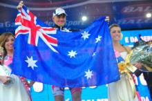 Adam Hansen holds up the Australian flag