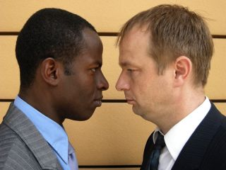 A black businessman and a white businessman face off.