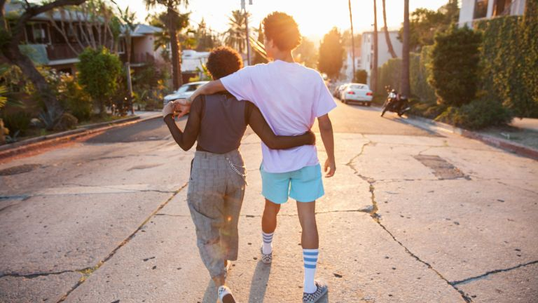 A young African American couple with their arms around each other walking down a suburban street at sunset shot from behind