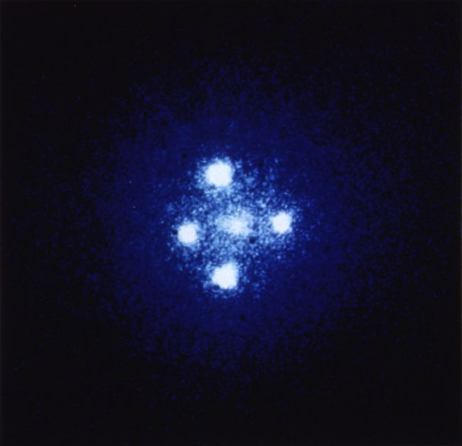 "This Hubble Space Telescope image, known as the ""Einstein Cross,"" shows four images of a distant quasar which has been multiplied by a nearby galaxy acting as a gravitational lens."