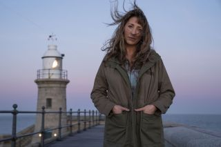 Back To Life: Miri Matteson (Daisy Haggard) stands in the foreground with a lighthouse behind her, her semi-crimped hair blowing into her face