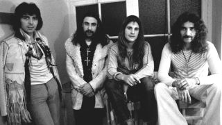 Black Sabbath standing in front of a window.