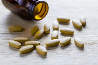 Vitamin C pills spill out of a jar