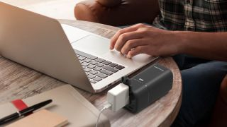 Best power bank: a man charging his Mac with a power bank