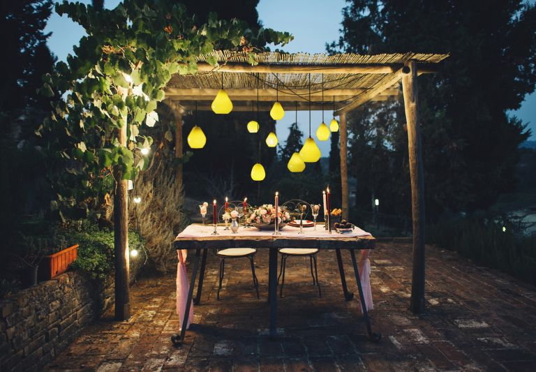 best outdoor lights with pendant lights hanging on a pergola above a dining table