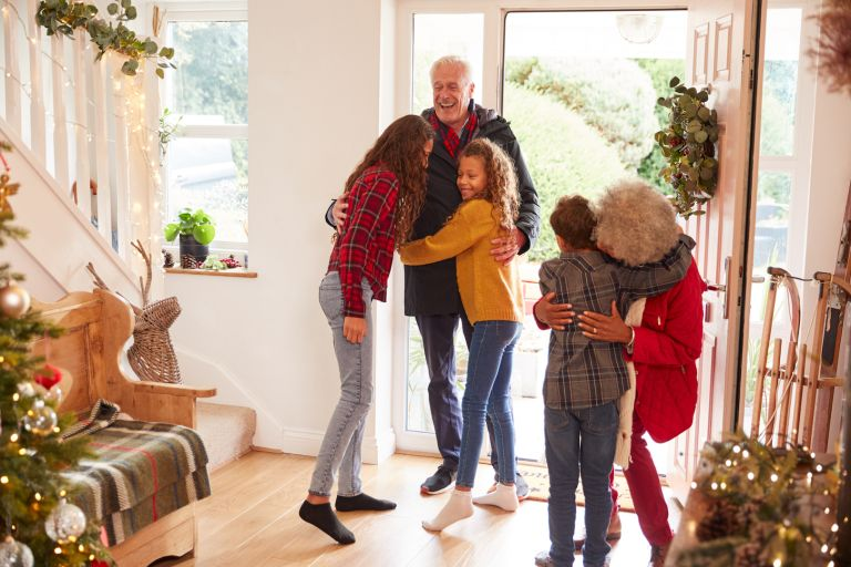 Excited Grandchildren Greeting Grandparents With Presents Visiting On Christmas Day under the new coronavirus Christmas rules UK 2020