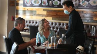 Nicki Raman serves Beth Derry and Scott Deckard at the Peppermint Downtown Thai restaurant on May 11, 2020, in Palm Beach, Florida. The restaurant opened as Palm Beach County, starts the first phase of the states coronavirus pandemic reopening plan.