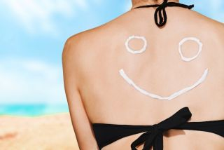 A woman wearing sunscreen on her back in the shape of a smiley face.