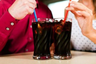 Two people drink sodas out of straws.