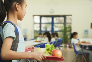 A girl takes her lunch toward a seat in a school cafeteria