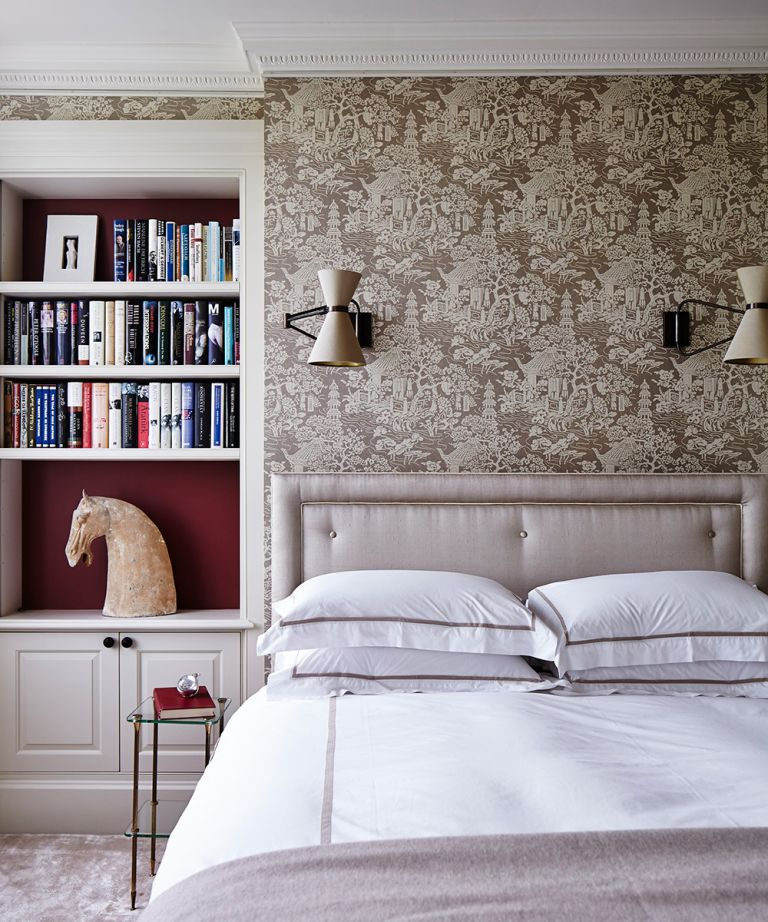 Bedroom wall lighting ideas showing a grey satin bed with white bedding in front of decorative wallpaper and two wall lamps