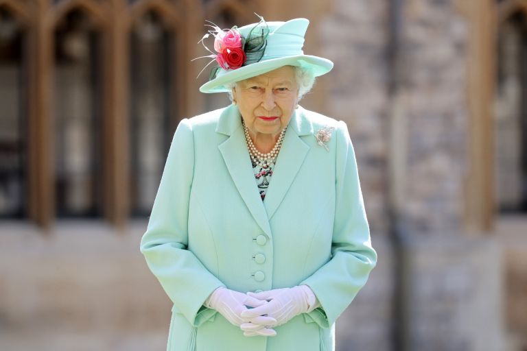 Queen Elizabeth II poses after awarding Captain Sir Thomas Moore with the insignia of Knight Bachelor at Windsor Castle on July 17, 2020 in Windsor, England