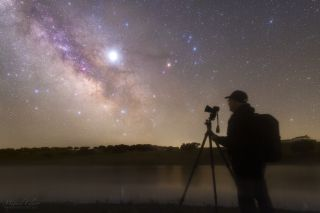An astrophotography student stands before the Milky Way galaxy and the bright planet Jupiter during an astrophotography workshop in Campinho, Portugal, on May 5, 2019.
