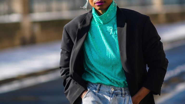 clothing trends: street style model wearing sequin top with jeans and a blazer