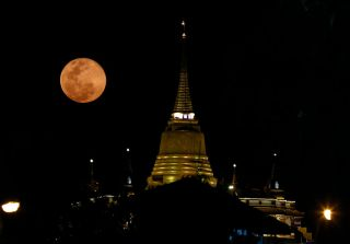 pink moon above a temple in Thailand.