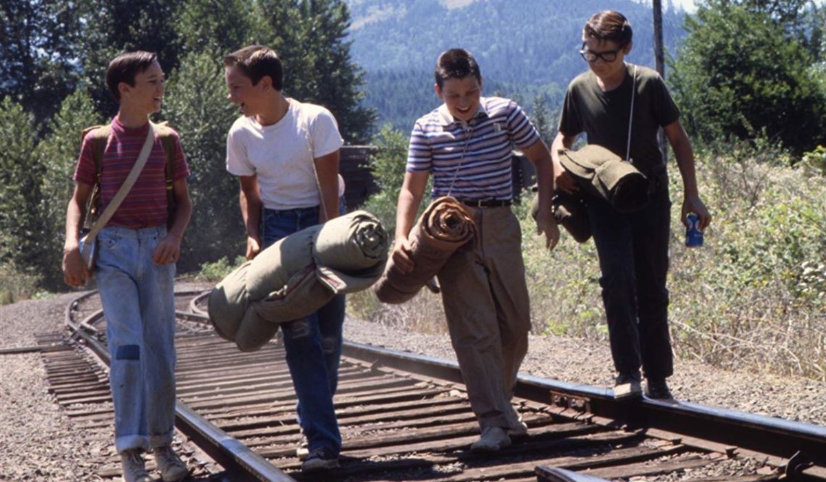 Wil Wheaton, River Phoenix, Jerry O'Connell, and Corey Feldman walk on the train tracks in Stand By Me.