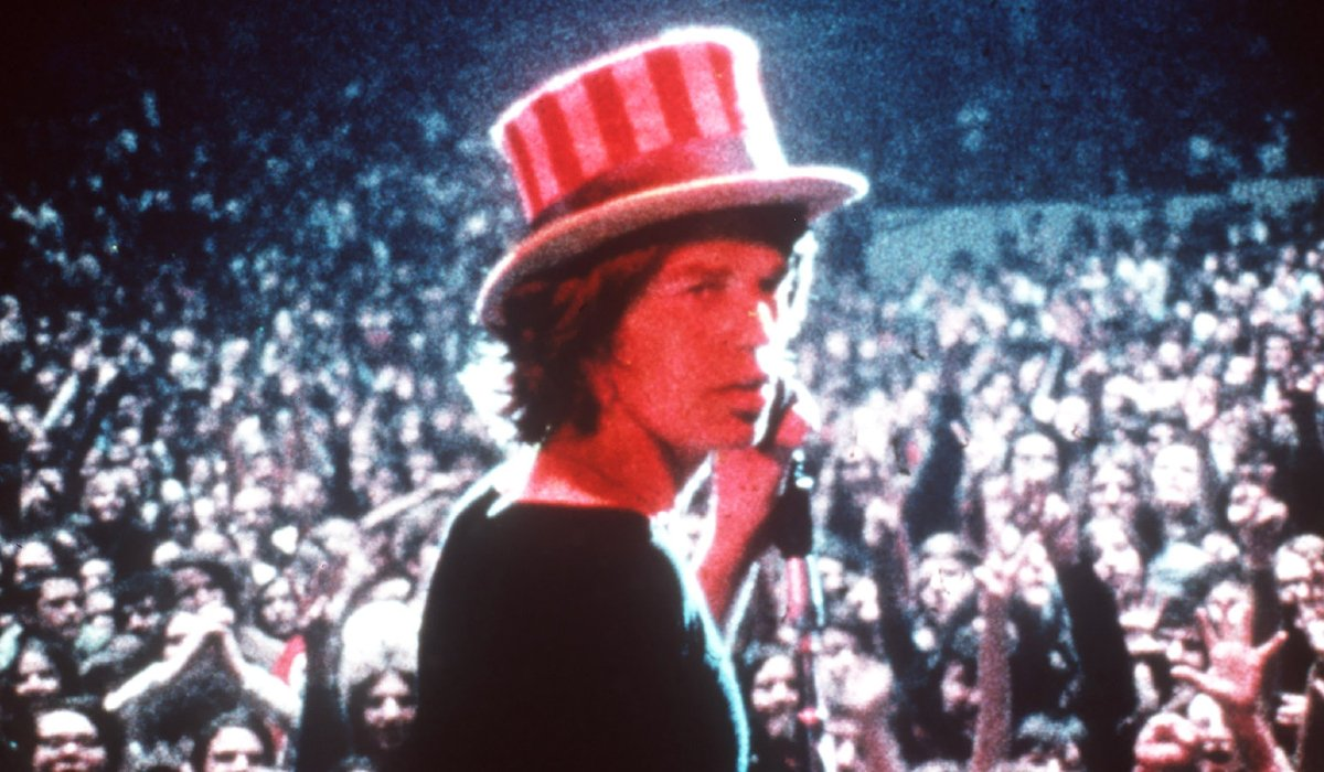 Gimme Shelter Mick Jagger looks back at the camera, with an Uncle Sam hat