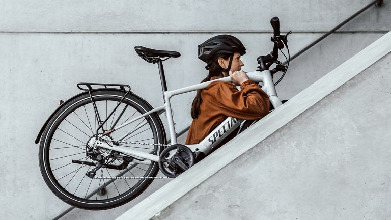 woman carrying Specialized ebike upstairs