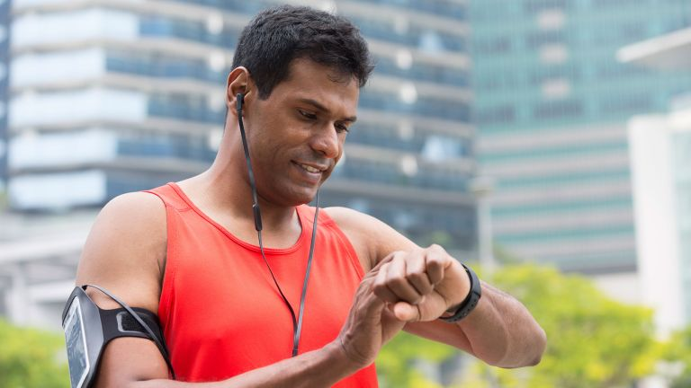 A runner checking his fitness watch during a heart rate training run