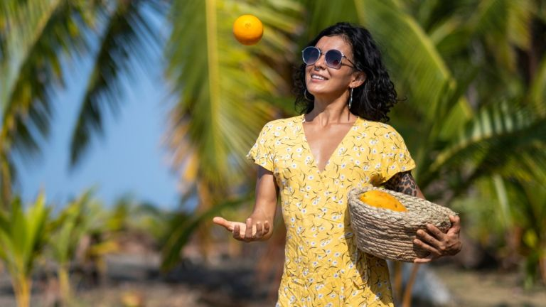 Young woman holding a fruit basket at the beach, Costa Rica - stock photo
