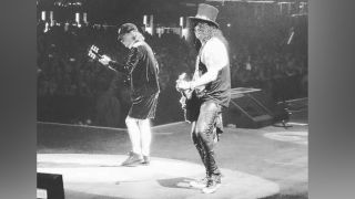 angus young of ac/dc on stage with guns n' roses