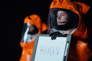 "A woman in an orange hazmat suit holds up a whiteboard with the word ""human"" written on it."