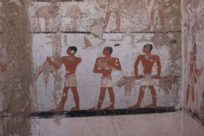 Three men are seen carrying what appear to be birds. They may be offerings for Hetpet.